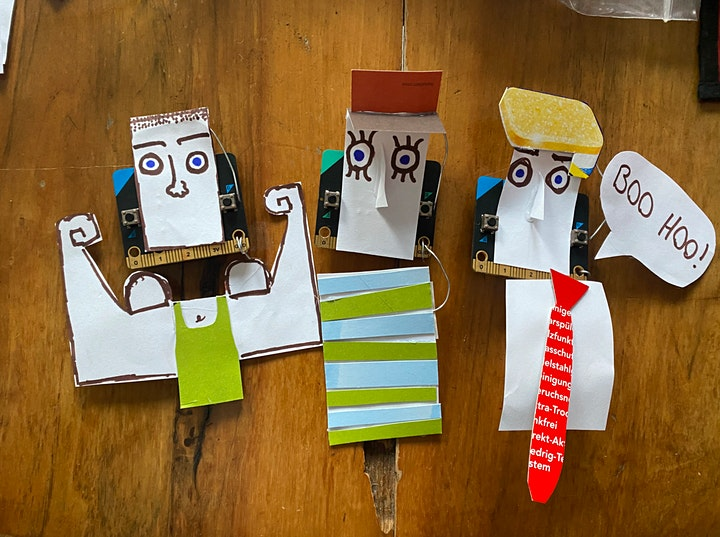 3 cartoon figures made from coloured parer stuck onto microbits.