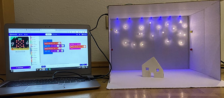 A laptop displaying the microbit software attached to a card box full of blue and white lights and a simple cardboard house.