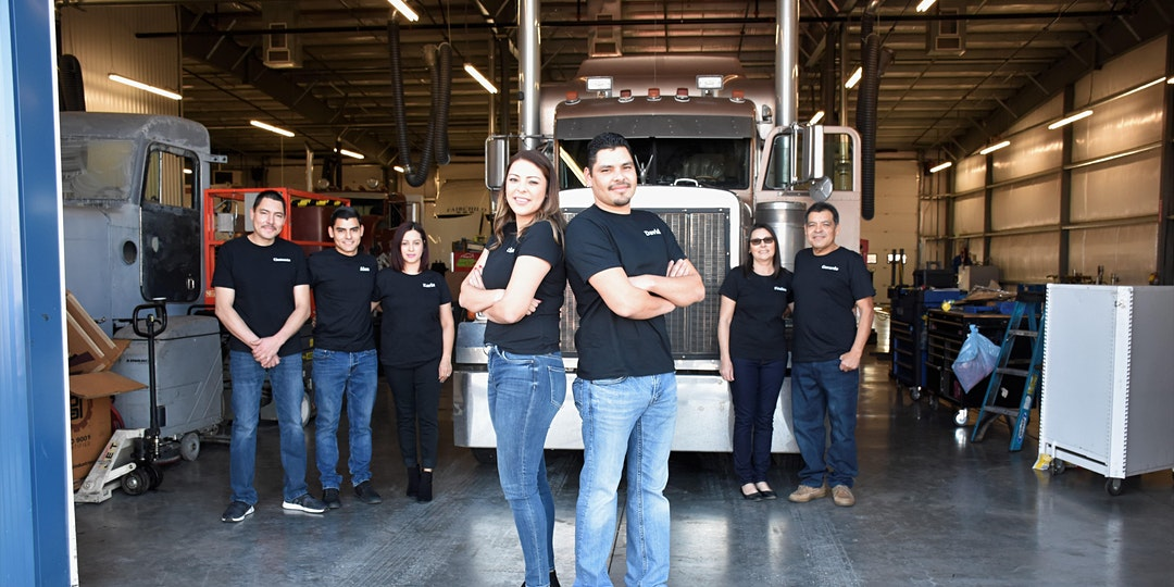 The Ruleas family poses in front of a semi in their workshop